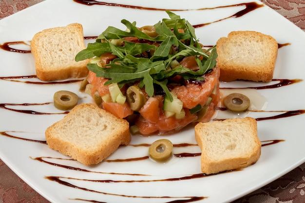 Salmon tartar with avocado, cucumber, olives and arugula.