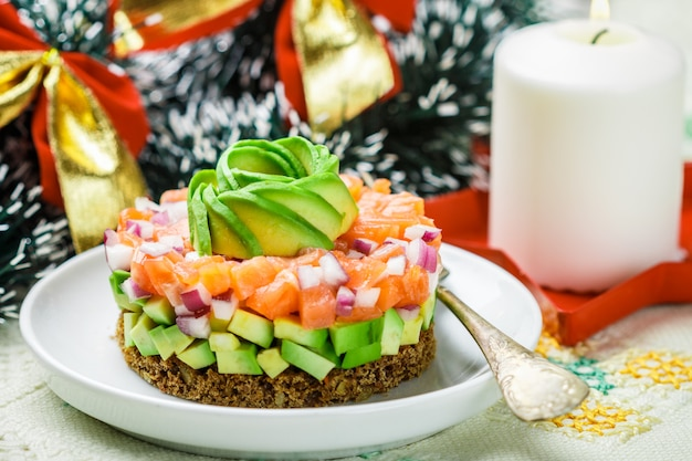 Salmon tartare (trout) with avocado and red onion on rye bread. appetizer for christmas and new year