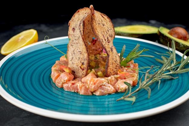 Тартар из лосося с авокадо, на тарелке в голубую полоску, с лаймом и гренками