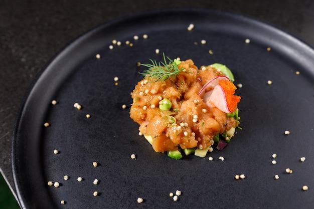 Тартар из лосося с авокадо, зеленым луком, помидорами и икрой