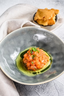 Salmon tartare with avocado, spring onion. white background. top view