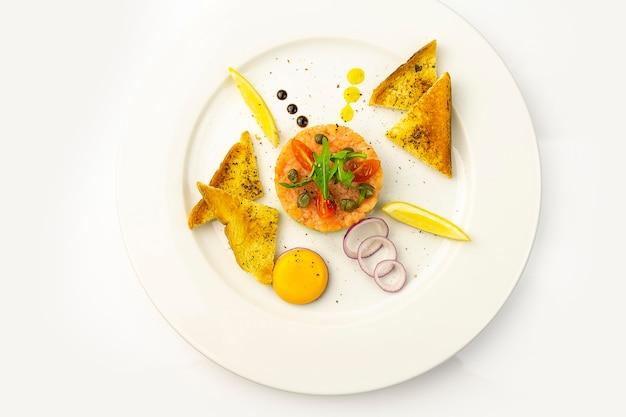 Тартар из лосося с авокадо с яйцом и тостами на белой тарелке, вид сверху