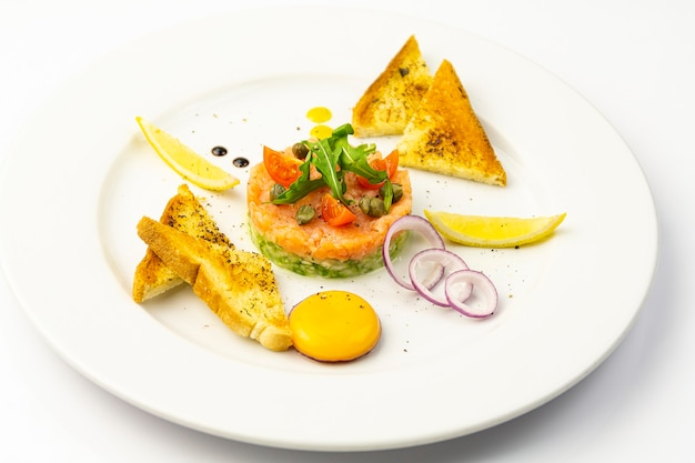 Тартар из лосося с авокадо, яйцом и тостами на белой тарелке