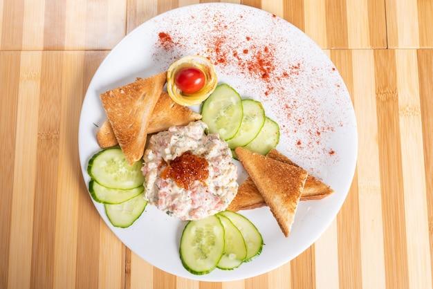 Тартар из лосося с крекерами и закусками. для любых целей.