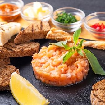 Тартар из лосося с хрустящим хлебом и лимоном. тартар из сырой рыбы. крупным планом
