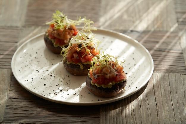 Тартар из лосося с соусом гуакамоле. тосты с гуакамоле и лососем на белой тарелке. роскошный стол в ресторане
