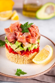 Тартар из лосося с помидорами, авокадо и киноа на тарелке