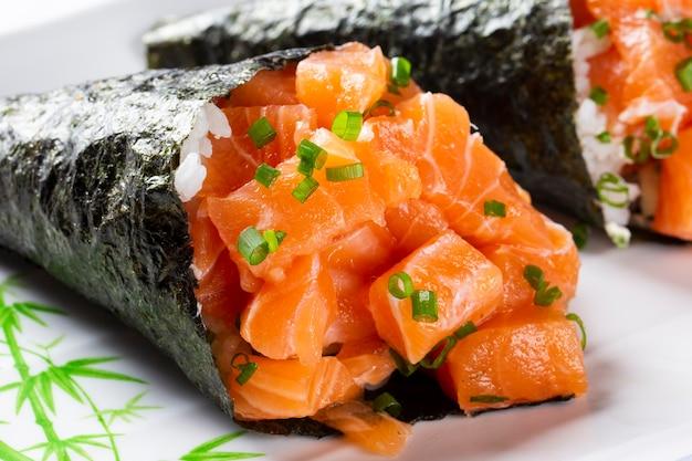 白いプレートの白いプレートにサーモンてまき寿司