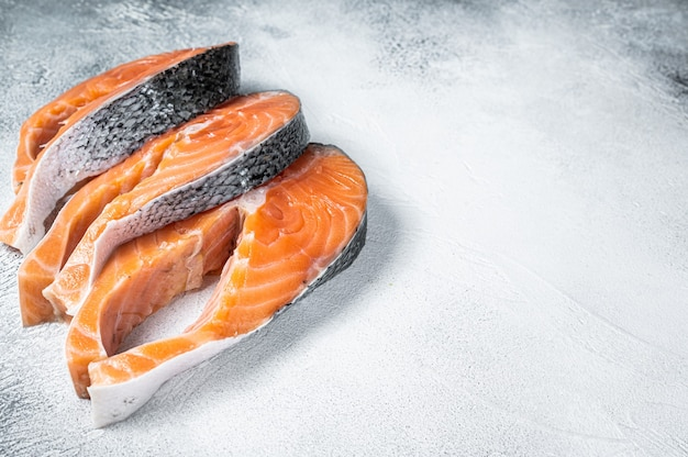 Salmon or trout steaks, raw fish prepared for cooking. white background. top view. copy space.