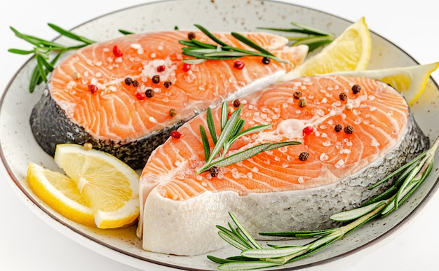 Salmon or trout steaks with pepper, sea salt, rosemary and lemon on white. top view, keto diet and healthy eating concept.