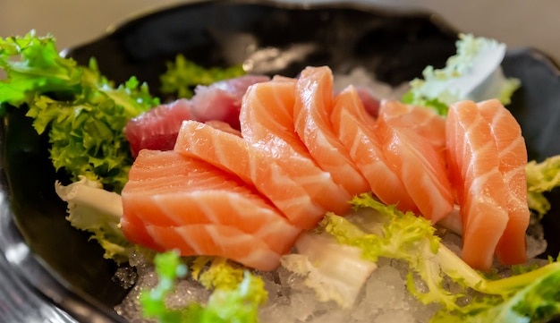 Salmon and tuna sashimi on a bed of salad and ice