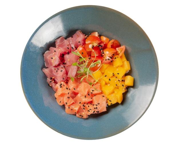Лосось, тунец, помидоры и манго тыкать в синюю миску изолированы