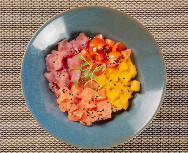 Лосось, тунец, помидоры и манго в синей миске