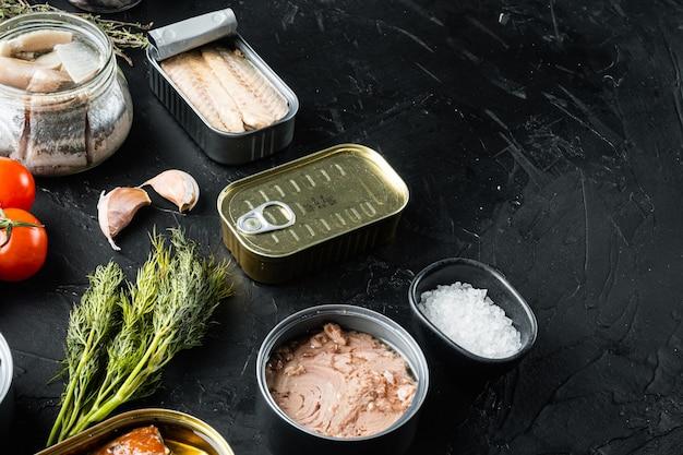 Лосось, тунец, скумбрия и анчоусы - рыбные консервы в жестяных банках, на черном