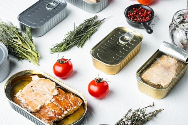 Лосось, тунец, скумбрия и анчоусы рыбные консервы в жестяных банках, на белом, с травами и ингредиентами
