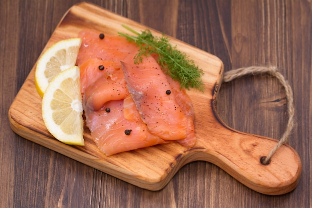 Salmon with lemon and black pepper on wooden board on brown wood
