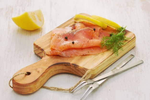Salmon with lemon and black pepper on wooden board