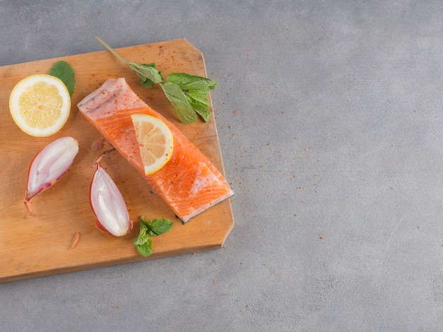 Salmon with lemon on wooden board
