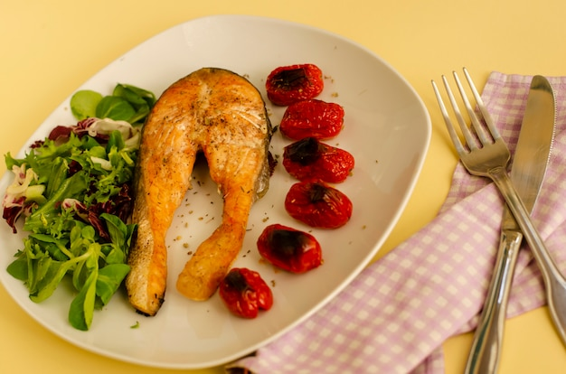 Salmon with roasted cherry tomatoes and mixed salad. mediterranean food concept