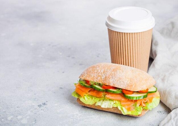 Свежий здоровый salmon сандвич с салатом и огурцом с бумажным стаканчиком кофе на белой каменной предпосылке. закуска к завтраку.