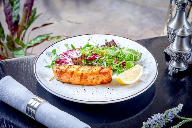 Закройте вверх по взгляду на цельном salmon стейке с зеленым салатом и лимоном на белой плите. ресторан еда фон. копировать пространство морепродукты. здоровая пища на обед. рыбная мука со свежими овощами