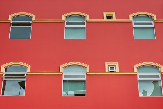 Фасад отеля лососевого цвета с симметричными окнами и балконами