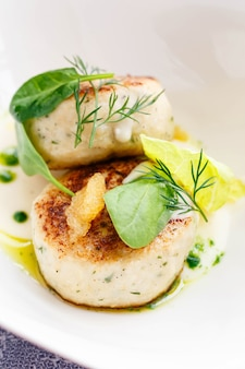 Котлеты из лососевой трески со шпинатом и щучьей икрой с белым соусом в ресторанной сервировке. кето, палео, диетическое питание fodmap. закройте вверх.