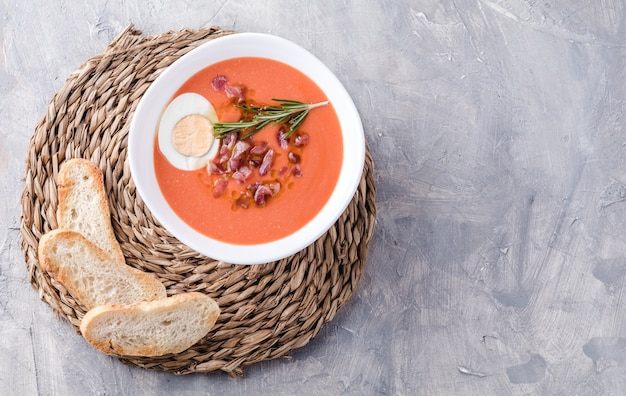 Salmorejo soup, spanish traditional dish. with ham and eggs in a bowl