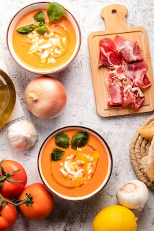Salmorejo soup with ham and eggs in a bowl. vertical top view