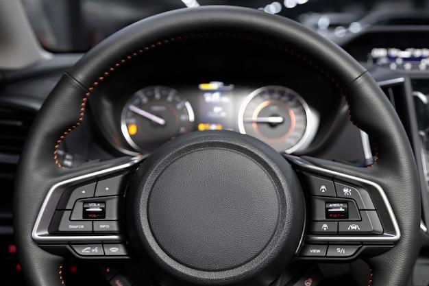 새로운 세련된 자동차의 살롱, 스티어링 휠, 속도계, 타코미터 및 기타 설정 버튼이 있는 대시보드