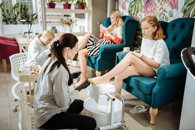 Saloon with mother. cute stylish teenage girl visiting beauty saloon with her mother and making pedicure