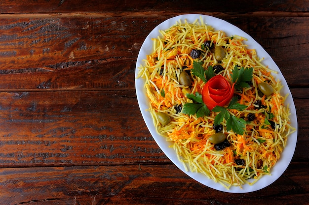 Salpicao is a typical brazilian salad, made with shredded chicken, raisin, grated carrot, potato sticks and mayonnaise.