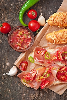 Salsa dip in bowl of bread and cheese sticks on wooden background