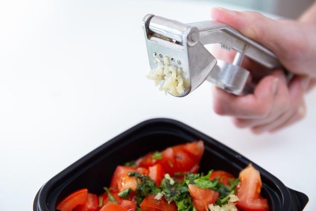 Соус сальсы. сочные красные нарезанные помидоры с зеленью, лимоном и чесноком. домашняя еда. свежие ингредиенты или овощи для соуса сальса. мужские руки держат чесночный пресс или чеснокодавилку.