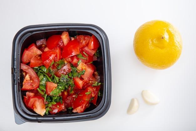 Соус сальсы. сочные красные нарезанные помидоры с зеленью, лимоном и чесноком. домашняя еда. свежие ингредиенты или овощи для соуса сальса.
