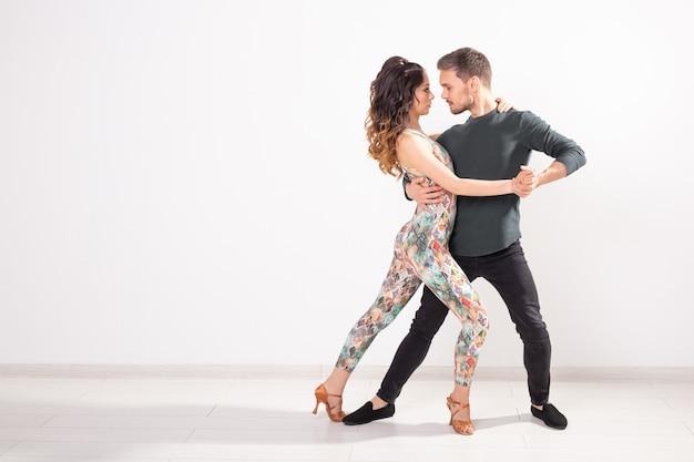 Танцоры сальсы, кизомбы и бачаты на белом фоне с копией пространства. концепция социального танца