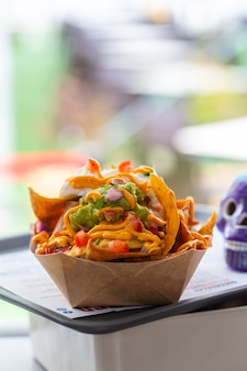 Salsa nachos in a street cafe in a paper plate, in the background is part of a blue skull figurine