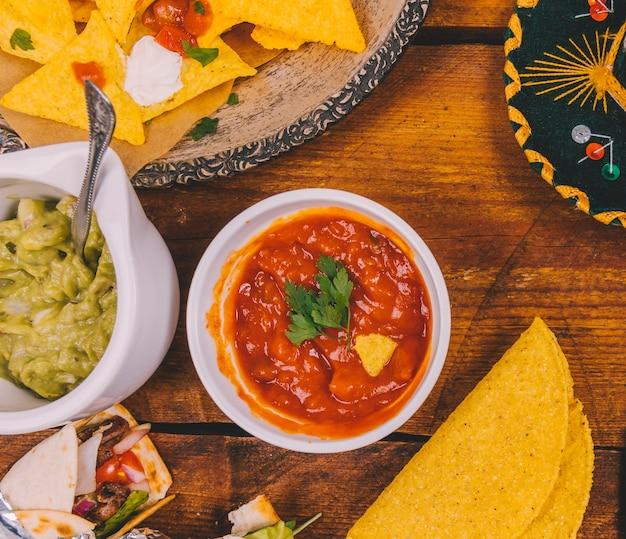살사 소스; 아보카도 소스; 맛있는 멕시코 나초; 옥수수와 나무 테이블에 멕시코 타코를 포장