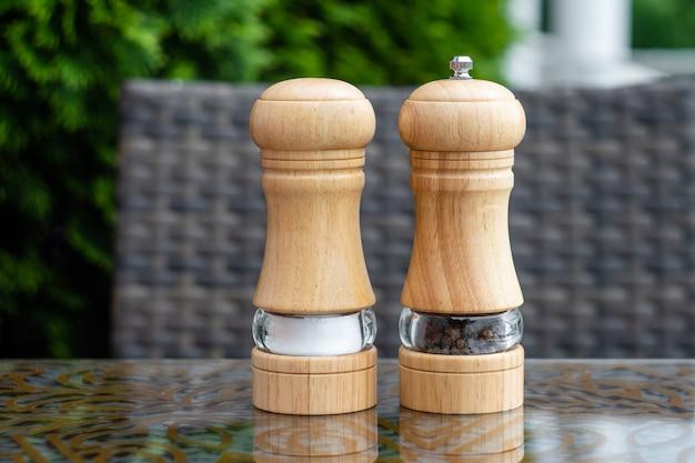 여름 카페의 소금과 후추 셰이커, 레스토랑 테이블에 있는 나무 후추 분쇄기