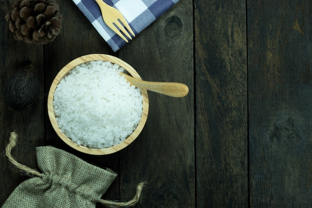 Salt in a bowl and spoon on wood background