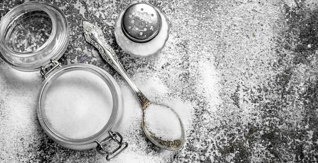 Salt in a glass jar. on rustic background.
