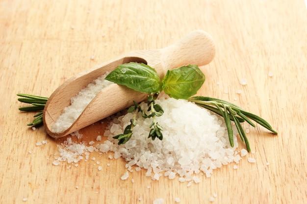 木製の背景に新鮮なバジル、ローズマリー、タイムとシャベルの塩