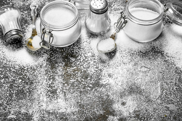 Salt in jars and spoons. on rustic background.