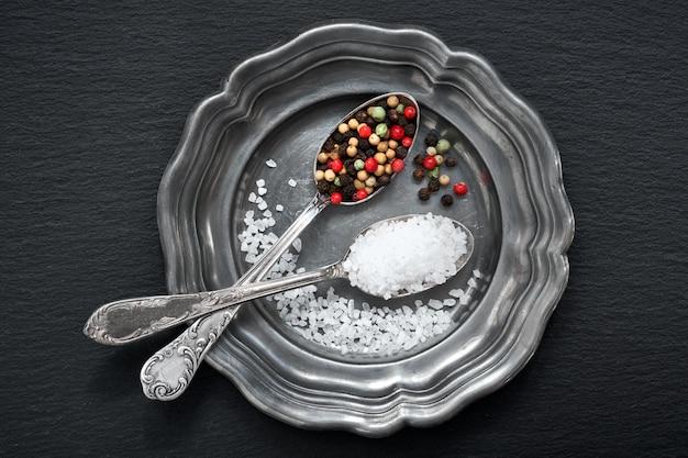 Salt in mixed pepper in vintage spoons on old metal plate on dark grey stone