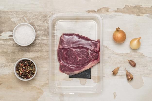 木製のテーブルに真空包装された塩、コショウ、牛肉のステーキ。肉用の密封包装。