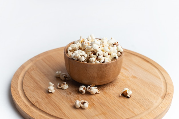 Salt popcorn on the wooden table. popcorn in a wooden bowl.