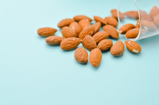 Salt roasted almonds in glass on blue background.