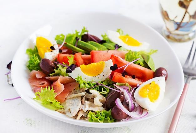 Салат из соленого лосося и запеченного дорадо с зеленью, помидорами, яйцом и авокадо