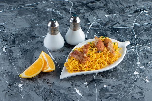 Соль, нарезанный лимон рядом с мясом и лапшой на блюде, на мраморном фоне.