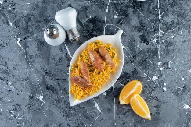 소금, 고기 옆에 얇게 썬 레몬, 접시에 국수, 대리석 표면.